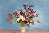 bouquet of flowers in vase - blue background