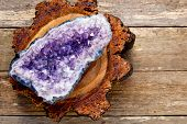 Amethyst Crystal Geode On Cross Section Of Timber Log With Wooden Plank Background poster