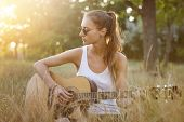 Hipster Female Teenager Enjoying Quiet Atmosphere On Nature Sitting With Guitar Singing Songs. Teena poster