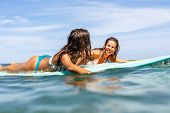 Two Beautiful Sporty Girls Surfing In The Ocean. poster