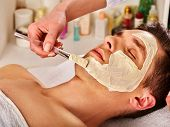 Mud facial mask of man in spa salon. Healing massage with clay full face. Male lying spa bed. Beauti poster