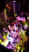 Nightclub dancefloor scene with dancing crowd in motion