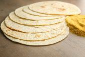 Composition with unleavened tortillas and corn flour on grey background poster