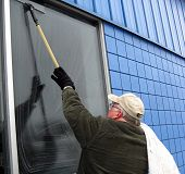 picture of window washing  - commercial window washer cleaning window with squeegee - JPG