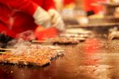 Closeup Kobe Beef Stick On A Hot Pan To Sale For Customer At Kuromon Market On Blurry Hands Of Chef  poster