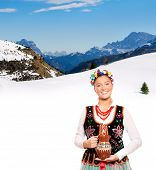A portrait of a beautiful and hospitable Polish woman in a traditional outfit over mountains in wint