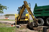 picture of dumper  - Excavator loading dumper truck tipper with sand on construction site - JPG