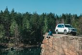 Woman Sitting On Rocky Edge With Lake View. White Suv Car Near. Adventure Concept poster