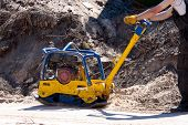 pic of vibration plate  - Worker at site Compacting a sand using a Plate Compactor - JPG