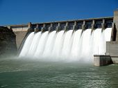 stock photo of dam  - Water pouring through flood gates of dam - JPG