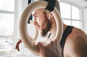 Tired Handsome Strong Man Holding On To Gymnastic Rings At Gym. Close Up Portrait Of Gymnast Male Ta poster