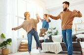 Happy Family Mother Father And Child Daughter Dancing At Home poster