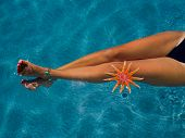 Womans legs with starfish at the swimming pool poster