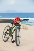 Bicycle with helmet, stand on the beach.