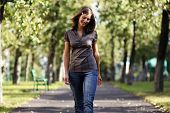 Full length, walking woman in blue jeans
