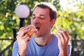 Young man eating burger in fast food