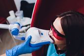 Dentist Curing Female Patient Woman Teeth Examined At Dentists Teeth Whitening. Stomatology Office T poster