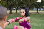 Focused woman in training session using pink dumbbells. Young determined latin woman lifting weights poster