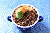 Blue china pot of muesli decorated with sallow thorn on blue table mat