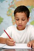 stock photo of school child  - Young boy at school writing on paper with map on backgroundl - JPG