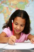foto of school child  - Child at school doing her homework with a map - JPG