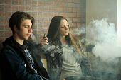 Vape Teenagers. Young Cute Girl In Sunglasses And Young Handsome Guy Smoke An Electronic Cigarettes poster