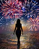 Festive fireworks over the sea and a silhouette of the woman going in waves