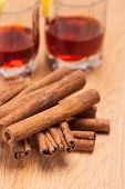 Glass Heating Red Liqueur With Cinnamon Sticks On Table