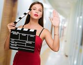 Young Woman Holding Clapper Board in einer Passage Weg