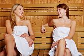 Two women sitting smiling in sauna and talking to each other