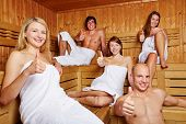 Happy people holding their thumbs up in a mixed sauna