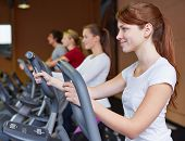 Young woman exercising on a crosstrainer in fitness center