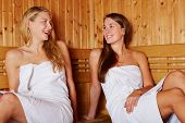 Two happy women talking to each other in a sauna