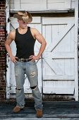 stock photo of redneck  - Handsome young country boy man wearing a stylish cowboy hat - JPG