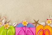 Flip Flops In The Sand With Shells And Frangipani Flowers. Summertime On Beach Concept.