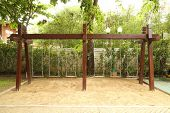 stock photo of swingset  - the wooden swing set on the playground - JPG