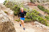 pic of canary-islands  - Young woman running on trail in mountains on summer day - JPG