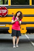 Girl Walking Away From School Bus While Texting On Her Phone
