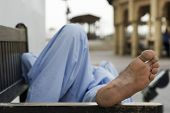 Dubai UAE man taking rest on park bench along boardwalk in Bur Dubai