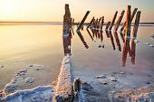 Sunset Over The Salt Lake. All Objects In This Lake Covered With Salt.