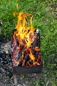 picture of brazier  - tongues of fire over burning wood in outdoor brazier - JPG