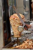 Chicken doner kebab on it's special bbq set with tray of sliced meat