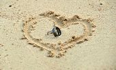 Wedding Rings Laying In Sand In Heart Shape