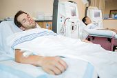 stock photo of dialysis  - Male patients sleeping while receiving renal dialysis in chemo room at hospital - JPG