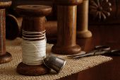 Sewing still life with antique thimble, scissors and wooden spools (from old textile mill - circa 19