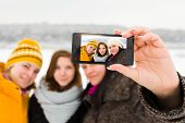 image of selfie  - Group of beautiful women taking selfies of themselves on mobile in winter - JPG