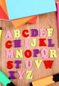 English alphabet, books and markers on wooden background