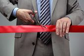 stock photo of scissors  - Cutting a red ribbon with scissors concept for new business venture or opening ceremony - JPG