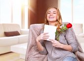 Happy female enjoying greeting card, reading with pleasure love letter, receive red rose, celebrate