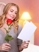 Portrait of cute blonde girl reading love letter with red rose in hand at home, receive festive post